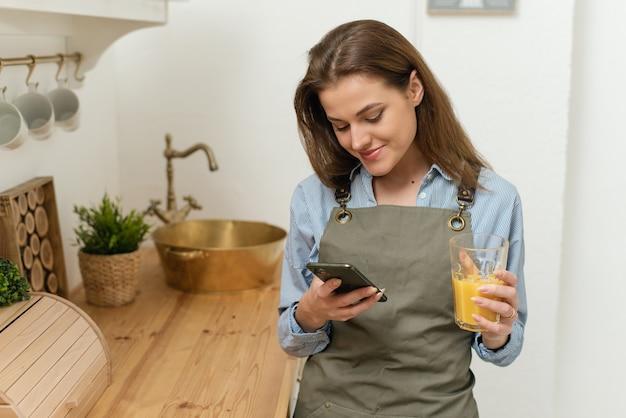 Porträt einer fröhlichen jungen frau, die in der küche mit einer tasse frischem orangensaft steht und textnachrichten auf ihrem telefon überprüft.