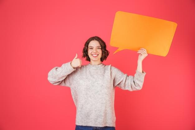 Porträt einer fröhlichen jungen frau, die isoliert über rosa steht und leere sprechblase hält
