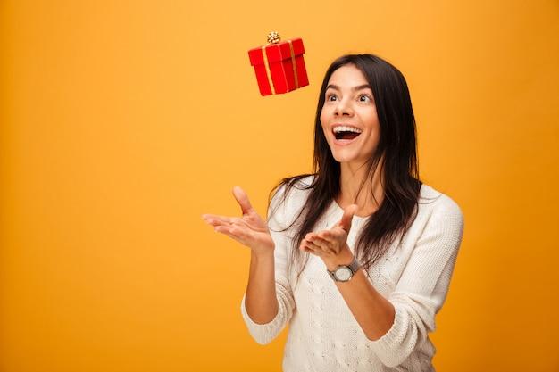 Porträt einer fröhlichen jungen frau, die kleine geschenkbox fängt