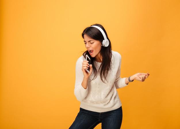 Porträt einer fröhlichen jungen frau, die musik hört