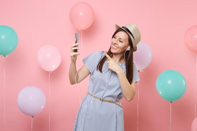 Porträt einer fröhlichen jungen frau im blauen kleid des strohsommerhuts mit handy und kopfhörern, die musik hören, die videoanrufe auf rosafarbenem hintergrund mit bunten luftballons macht. geburtstagsfeier.