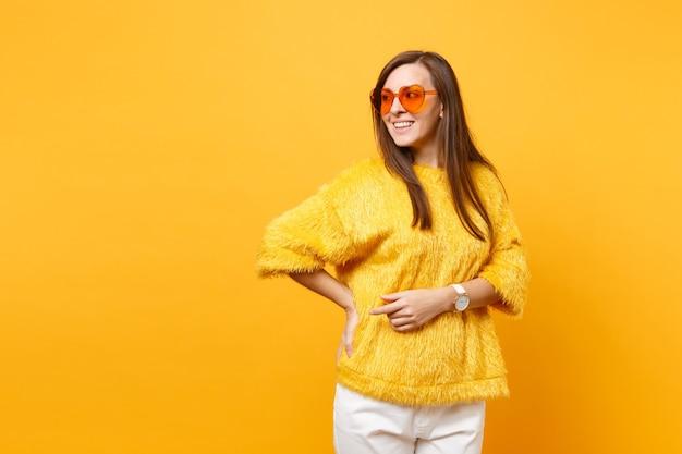 Porträt einer fröhlichen jungen frau in pelzpullover, weißer hose und herzorangefarbener brille, die isoliert auf hellgelbem hintergrund beiseite schaut. menschen aufrichtige emotionen, lifestyle-konzept. werbefläche.