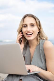 Porträt einer fröhlichen jungen geschäftsfrau, die mit einem laptop am strand lächelt und telefoniert
