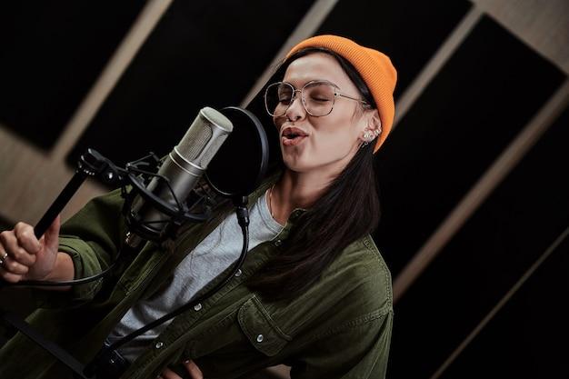 Porträt einer fröhlichen jungen hip-hop-künstlerin, die während der aufnahme in ein kondensatormikrofon singt