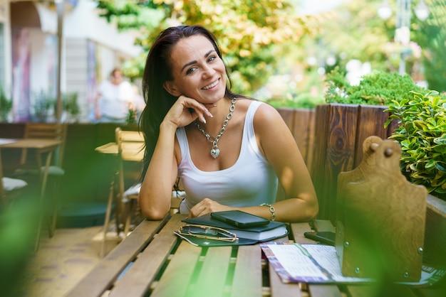 Porträt einer fröhlichen kaukasischen frau, die auf die straße schaut, während sie im café mit handy und n...