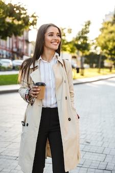 Porträt einer fröhlichen kaukasischen frau mit mantel, die kaffee zum mitnehmen trinkt und beim gehen auf der stadtstraße beiseite lächelt