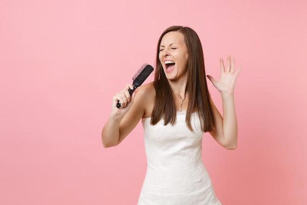 Porträt einer fröhlichen lustigen frau mit geschlossenen augen im weißen kleid, die lied mit kamm singt