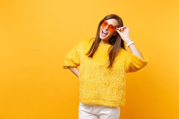 Porträt einer fröhlichen, lustigen jungen frau im pelzpullover, weiße hosen, die eine orangefarbene brille des herzens einzeln auf hellgelbem hintergrund halten. menschen aufrichtige emotionen, lifestyle-konzept. werbefläche.
