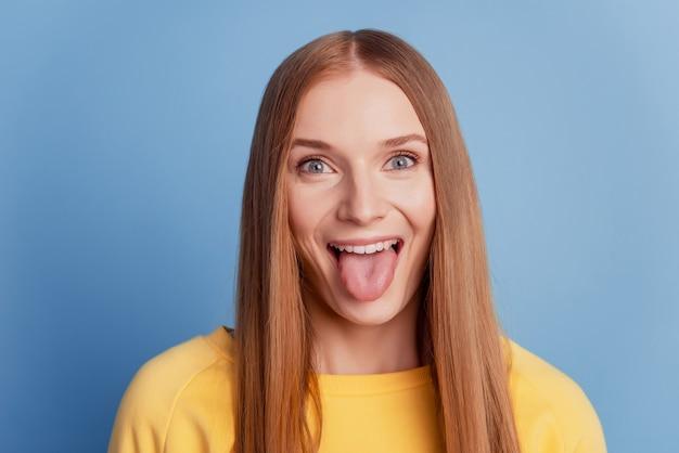 Porträt einer fröhlichen positiven dame mit zungenblickkamera auf blauem hintergrund