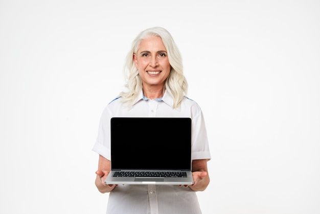Porträt einer fröhlichen reifen frau, die laptop des leeren bildschirms zeigt