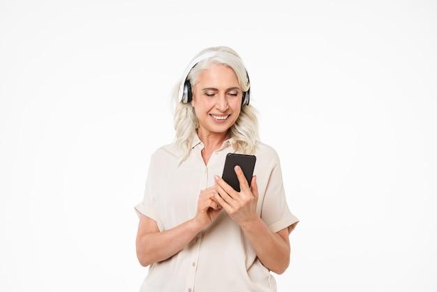 Porträt einer fröhlichen reifen frau, die musik hört