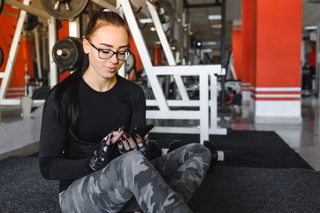 Porträt einer fröhlichen sportfrau, die smartphone im fitnessstudio verwendet
