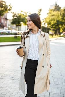Porträt einer fröhlichen süßen frau mit mantel, die kaffee zum mitnehmen trinkt und beim gehen auf der stadtstraße beiseite lächelt