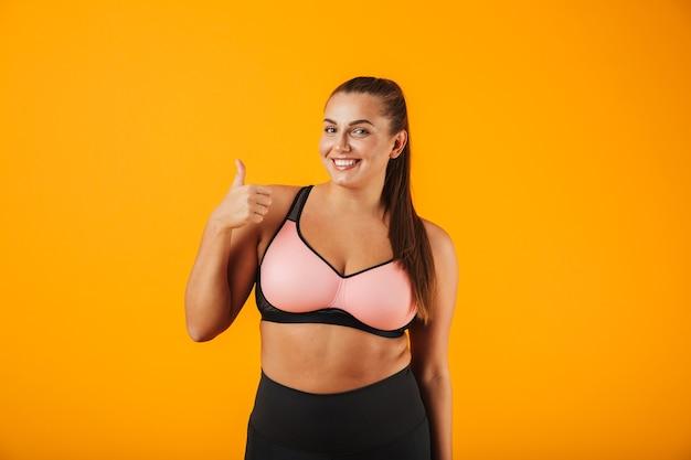 Porträt einer fröhlichen übergewichtigen fitnessfrau, die sportkleidung trägt, die lokal über gelber wand steht, daumen hoch