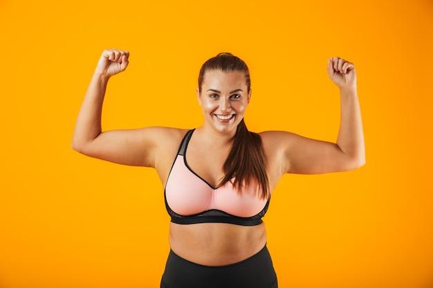 Porträt einer fröhlichen übergewichtigen fitnessfrau, die sportkleidung trägt, die lokal über gelber wand steht und bizeps biegt