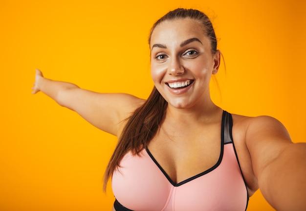 Porträt einer fröhlichen übergewichtigen fitnessfrau, die sportkleidung trägt, die lokal über gelber wand steht und ein selfie mit handy nimmt