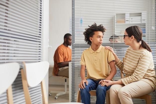 Porträt einer fürsorglichen erwachsenen frau, die den sohn tröstet, während sie in der medizinischen klinik in der schlange steht, kopierraum