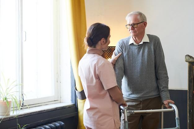Porträt einer fürsorglichen jungen frau, die älteren mann mit gehhilfe im pflegeheim-kopierraum unterstützt