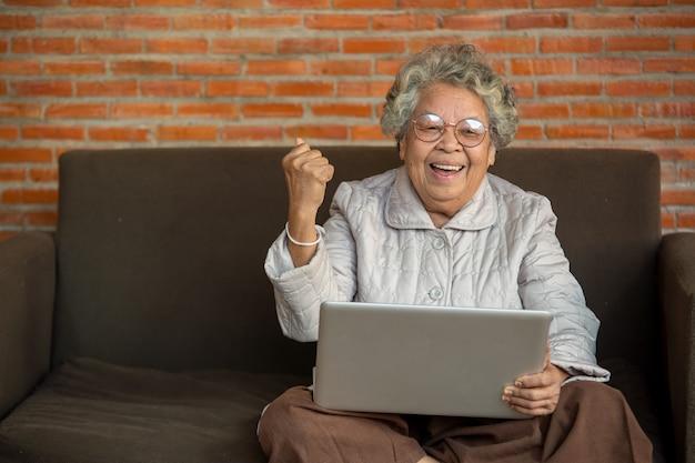 Porträt einer gealterten frau, die zoom-video-meeting online ansieht, glückliche ältere frau mittleren alters, die auf der couch sitzt und während des videoanrufs mit freunden der familie ein laptop-gerät verwendet.