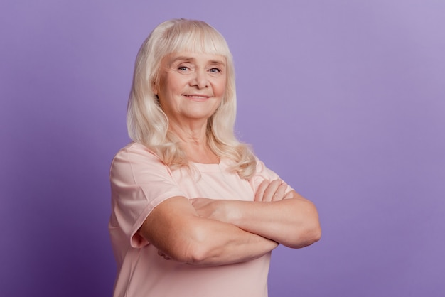 Porträt einer gealterten reifen frau mit verschränkten armen über violettem hintergrund