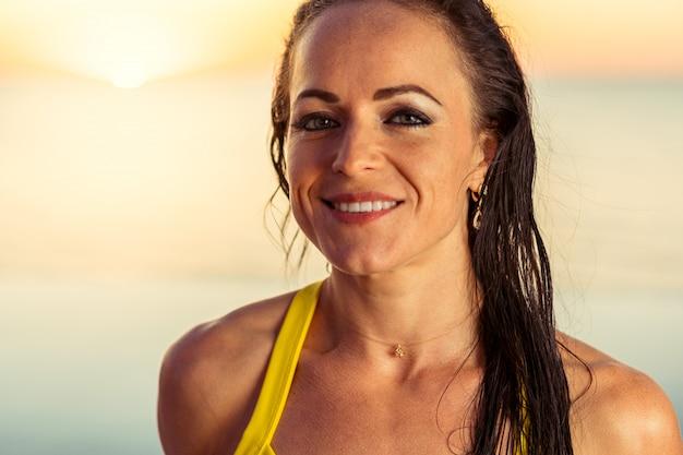 Porträt einer gebräunten brünetten frau im bikini nahe dem pool