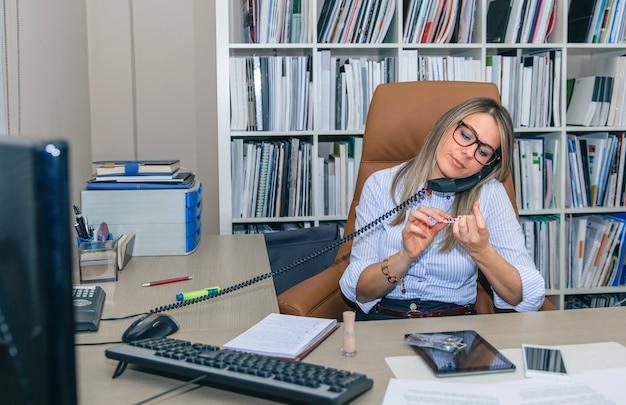 Porträt einer gelangweilten blonden sekretärin, die beim telefonieren die nägel am arbeitsplatz poliert