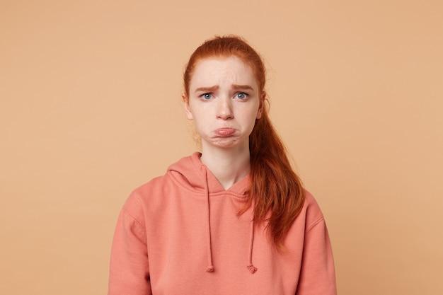 Porträt einer gereizten hübschen rothaarigen frau im sweatshirt, die unzufriedenheit ausdrückt