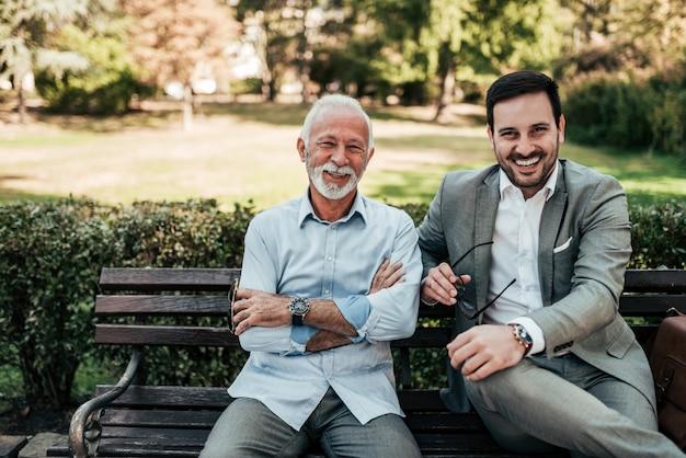 Porträt einer geschäftsfamilie draußen. zwei männer, die im park betrachtet kamera sitzen.