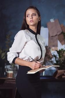 Porträt einer geschäftsfrau, die an in ihrem notizbuch schreibt.