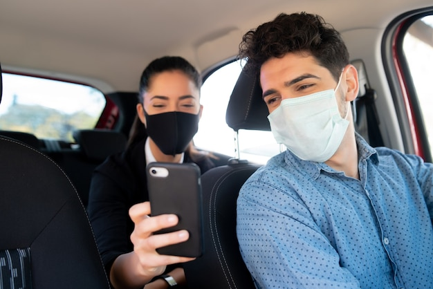 Porträt einer geschäftsfrau, die dem taxifahrer etwas auf seinem telefon zeigt.
