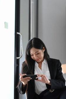Porträt einer geschäftsfrau, die eine pause im büro macht und social media auf einem smartphone beobachtet.