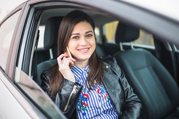 Porträt einer geschäftsfrau, die im auto spricht auf mobiltelefon sitzt