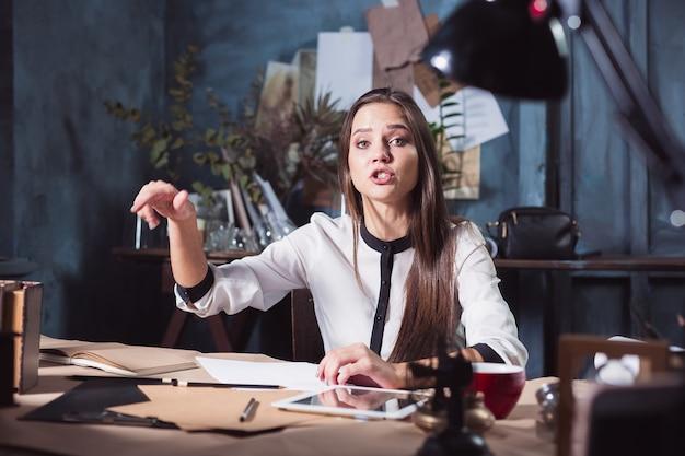 Porträt einer geschäftsfrau, die im büro arbeitet und details ihres bevorstehenden treffens in ihrem notizbuch überprüft und im loft-studio arbeitet.
