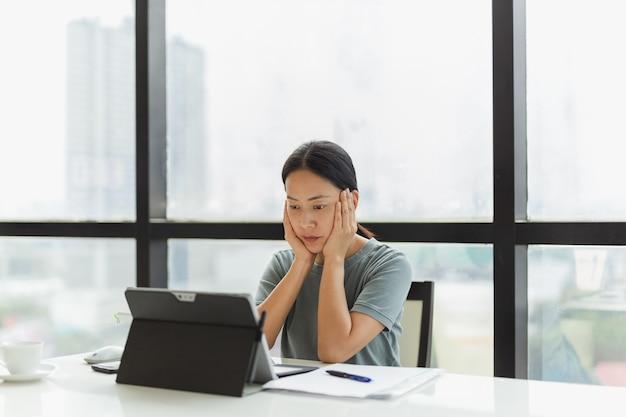 Porträt einer geschäftsfrau, die im büro mit den händen auf der wange an ihrem tablet arbeitet