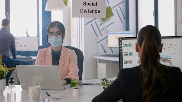 Porträt einer geschäftsfrau, die in einem modernen büro mit einer medizinischen gesichtsmaske in das laptop-display schaut. mitarbeiter, die im hintergrund bei einem managementprojekt arbeiten und die soziale distanzierung respektieren