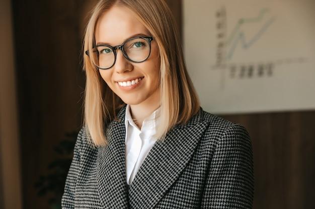 Porträt einer geschäftsfrau in brille, in einem strengen geschäftsanzug, lächelnd mit den zähnen im büro. büro erfolgreich glücklicher arbeiter.