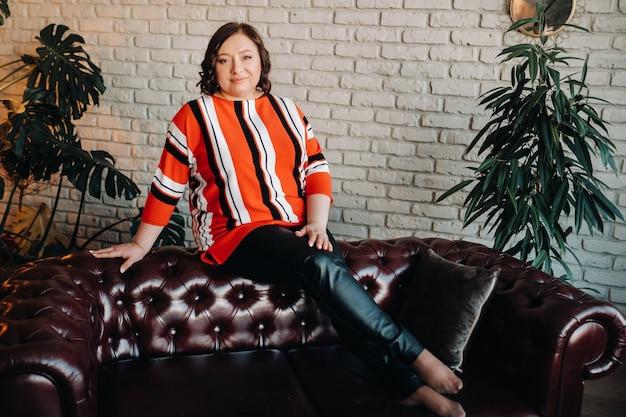 Porträt einer geschäftsfrau in einer gestreiften jacke, die auf einem sofa im innenraum sitzt.