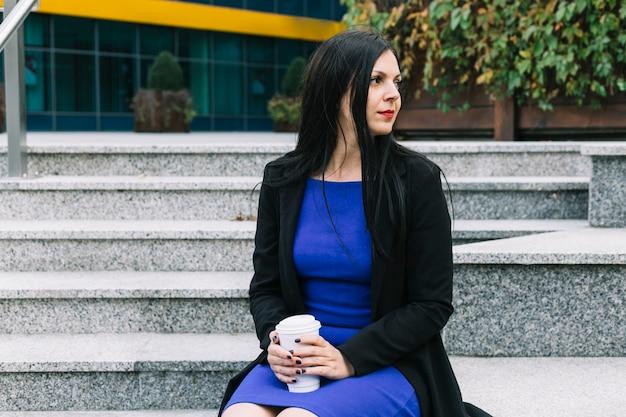 Porträt einer geschäftsfrau mit dem entsorgungscup, der weg schaut
