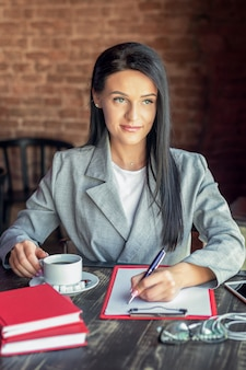 Porträt einer geschäftsfrau schreibt auf weißem rohling, während tasse kaffee im café hält