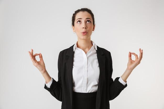 Porträt einer gestressten jungen geschäftsfrau, die meditiert