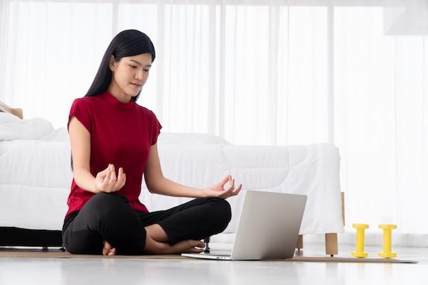 Porträt einer gesunden jungen asiatischen frau, die yoga-übungen praktiziert, die im schlafzimmer sitzen und zu hause online auf dem laptop lernen. konzept der bewegung und entspannung, technologie für einen neuen normalen lebensstil