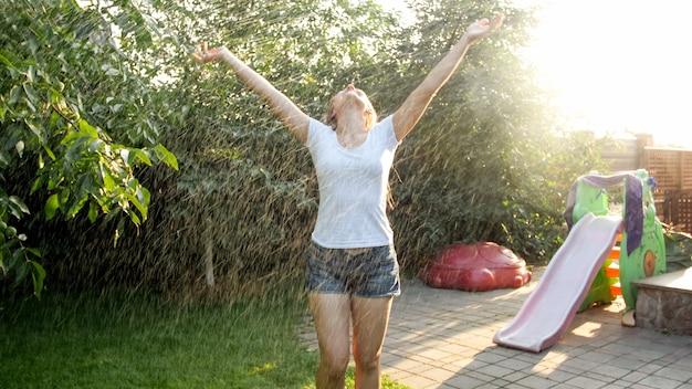 Porträt einer glücklich lachenden jungen frau mit langen haaren in nasser kleidung, die unter warmem regen im garten tanzt. familie, die im sommer im freien spielt und spaß hat