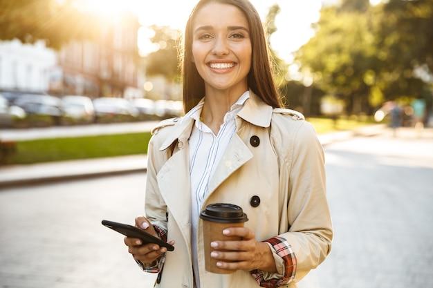 Porträt einer glücklich lächelnden frau mit mantel, die kaffee zum mitnehmen trinkt und beim gehen auf der stadtstraße auf dem handy tippt