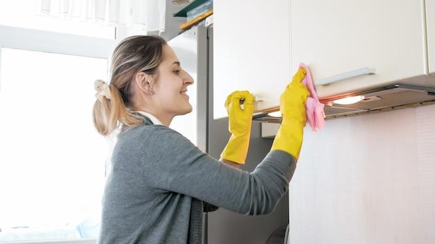Porträt einer glücklich lächelnden jungen frau, die oberflächen in der küche säubert und poliert, während sie hausarbeit macht.