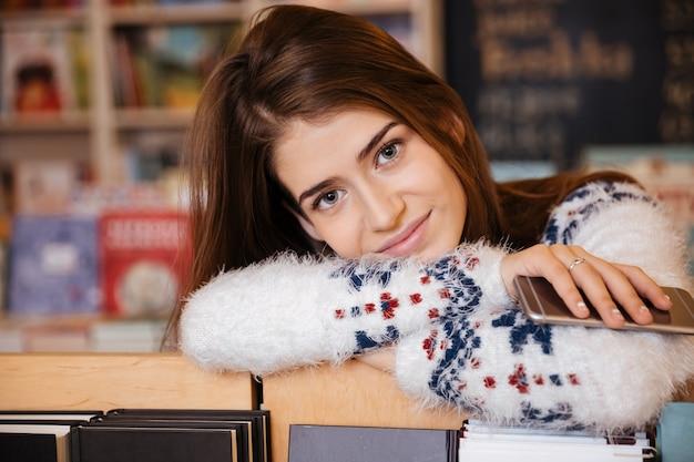 Porträt einer glücklich lächelnden studentin, die sich auf das bücherregal stützt