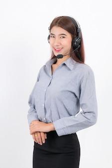 Porträt einer glücklich lächelnden telefonistin mit kurzen haaren, die ein weißes hemd mit einem headset trägt, das auf einer seite steht und den kopfhörer isoliert auf weißer oberfläche hält