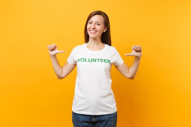 Porträt einer glücklich lächelnden, zufriedenen frau im weißen t-shirt mit der schriftlichen aufschrift grüner titelfreiwilliger lokalisiert auf gelbem hintergrund. freiwillige kostenlose hilfe, konzept der wohltätigkeitsarbeit.