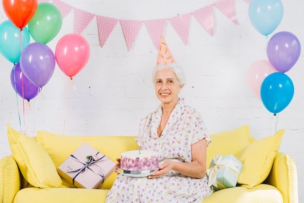 Porträt einer glücklichen älteren frau, die auf sofa mit geburtstagskuchen sitzt
