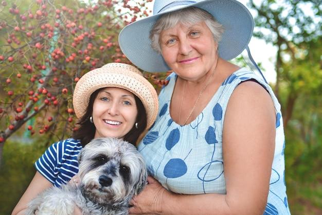 Porträt einer glücklichen älteren frau, die ihre tochter und ihren hund umarmt