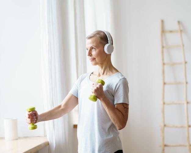 Porträt einer glücklichen älteren frau, die zu hause fitnessübungen mit hanteln macht
